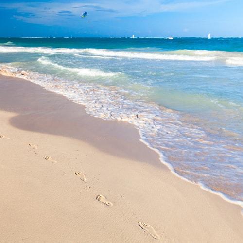 Ein Sandstrand mit einem blauen Meer. Es sind Fussspuren im Sand entlang des Wassers zu sehen.