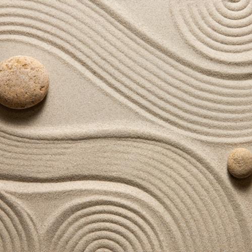 Zwei Steine auf einen Sandboden. Im Sand sind Wellen und Kreis geformt